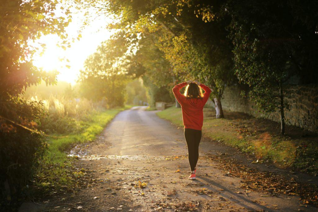 朝活で太陽の光を浴びながら走る女性